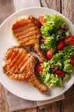 Εύγευστο ψημένο στη σχάρα μέλι χοιρινό κρέας μπριζολών που εξυπηρετείται με μια σαλάτα του φρέσκου β Στοκ φωτογραφίες με δικαίωμα ελεύθερης χρήσης