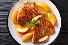 Εύγευστο ψημένο στη σχάρα χοιρινό κρέας μπριζολών με τα φρέσκα ροδάκινα και το σκόρδο μελιού Στοκ Εικόνες