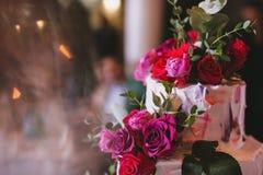 Εύγευστο όμορφο γαμήλιο κέικ με την άσπρη κρέμα που διακοσμείται με τα ρόδινους και κόκκινους τριαντάφυλλα και τον ευκάλυπτο Στοκ φωτογραφία με δικαίωμα ελεύθερης χρήσης