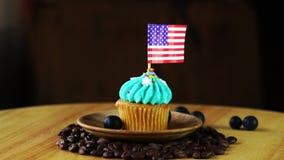 Εύγευστο cupcake σε ένα ξύλινο πιάτο σε έναν σωρό των φασολιών καφέ σε ένα απόθεμα βίντεο