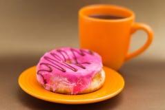 Εύγευστο doughnut με το ροζ βερνίκωσε πέρα από ένα πορτοκαλί πιάτο, με ένα πορτοκαλί φλιτζάνι του καφέ σε ένα μαλακό καφετί υπόβα Στοκ Εικόνες