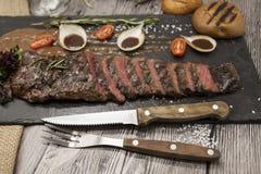 Εύγευστο juicy καυτό βόειο κρέας ψητού που κόβεται στα εύγευστα κομμάτια του κρέατος και των λαχανικών Εξυπηρετημένος σε ένα μαύρ Στοκ Φωτογραφία