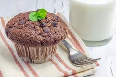 Εύγευστο muffin σοκολάτας με τα τσιπ choco και το ποτήρι του γάλακτος Στοκ εικόνα με δικαίωμα ελεύθερης χρήσης