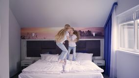 Εύθυμα δίδυμα που πηδούν στο κρεβάτι απόθεμα βίντεο