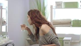 Εύθυμα δόντια βουρτσίσματος γυναικών και ξέπλυμα με το νερό του μπροστινού καθρέφτη στο λουτρό φιλμ μικρού μήκους