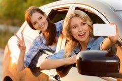 Εύθυμα κορίτσια που κάθονται στο αυτοκίνητο Στοκ Φωτογραφίες