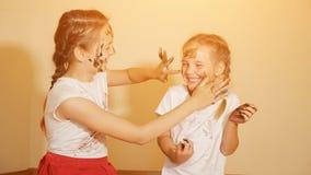Εύθυμα κορίτσια που χρωματίζουν το ένα το άλλο με τα χρώματα στοκ εικόνα με δικαίωμα ελεύθερης χρήσης