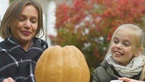 Εύθυμα κυρία και κορίτσι που χαράζουν την κολοκύθα αποκριών, προετοιμασία για τον εορτασμό απόθεμα βίντεο
