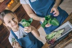 Εύθυμα μαγειρεύοντας λαχανικά κοριτσιών με τη μητέρα Στοκ φωτογραφία με δικαίωμα ελεύθερης χρήσης