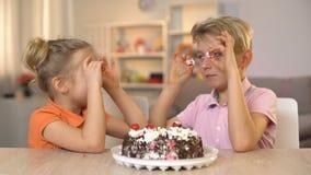 Εύθυμα μπροστινά μάτια κερασιών κέικ εκμετάλλευσης αδελφών και αδελφών, που παίζουν από κοινού απόθεμα βίντεο