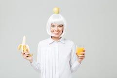 Εύθυμα νέα μπανάνα εκμετάλλευσης γυναικών και ποτήρι του χυμού Στοκ Φωτογραφία