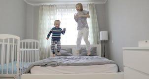 Εύθυμα παιδιά που οργανώνονται στο κρεβάτι και το άλμα απόθεμα βίντεο