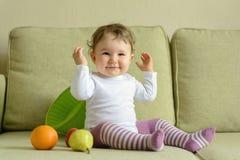 Εύθυμα παιχνίδια κοριτσάκι με τα φρούτα στο σπίτι Στοκ Εικόνα