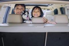 Εύθυμα παιδιά και γεροδεμένο σκυλί στο αυτοκίνητο Στοκ Φωτογραφία