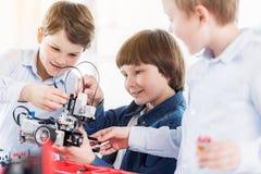 Εύθυμα παιδιά που κρατούν το ρομπότ Στοκ Φωτογραφία