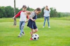Εύθυμα παιδιά που παίζουν το ποδόσφαιρο με τη σφαίρα στην πράσινη χλόη Στοκ εικόνες με δικαίωμα ελεύθερης χρήσης