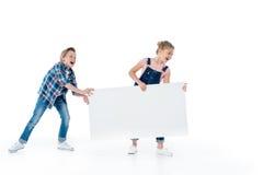 Εύθυμα χαριτωμένα παιδιά που έχουν τη διασκέδαση με την κενή αφίσσα Στοκ Εικόνες