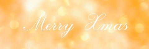 Εύθυμα Χριστούγεννα, που γράφουν στο χρυσό θολωμένο υπόβαθρο στοκ φωτογραφίες