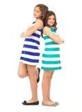 Εύθυμες αδελφές πλάτη με πλάτη που απομονώνεται που στέκονται Στοκ φωτογραφία με δικαίωμα ελεύθερης χρήσης