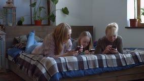 Εύθυμες γυναίκες που κοιτάζουν βιαστικά το δίχτυ στα έξυπνα τηλέφωνα απόθεμα βίντεο