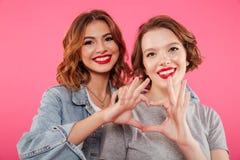 Εύθυμες δύο γυναίκες που αγκαλιάζουν παρουσιάζοντας χειρονομία αγάπης καρδιών Στοκ Φωτογραφία