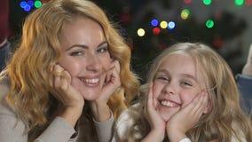 Εύθυμες μητέρα και κόρη που έχουν τη διασκέδαση, που σπρώχνει με τη μουσούδα κοντά στο χριστουγεννιάτικο δέντρο, διακοπές απόθεμα βίντεο