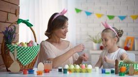 Εύθυμες μητέρα και κόρη που προετοιμάζονται για το παιχνίδι Πάσχας με τα διακοσμημένα αυγά απόθεμα βίντεο