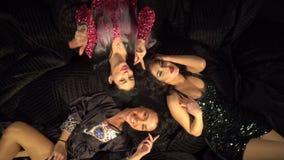 Εύθυμες τρεις φίλες brunette βάζουν στο κρεβάτι, το γέλιο και την τοποθέτηση επάνω από την μπλε τονισμένη όψη εργαλείων φιλμ μικρού μήκους