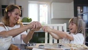 Εύθυμες Mum και η κόρη κάνουν mustache από τη ζύμη κατά να ψήσουν τα μπισκότα μαζί στην κουζίνα στο σπίτι Mom με απόθεμα βίντεο