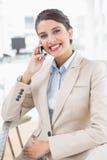 Εύθυμη έξυπνη καφετιά μαλλιαρή επιχειρηματίας που κάνει ένα τηλεφώνημα Στοκ φωτογραφίες με δικαίωμα ελεύθερης χρήσης