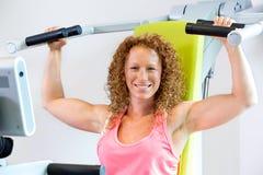 Εύθυμη αθλητική γυναίκα που χρησιμοποιεί τη μηχανή βάρους Στοκ Εικόνες