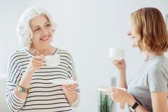 Εύθυμη ανώτερη γυναίκα και ο ενήλικος καφές κατανάλωσης κορών της Στοκ φωτογραφία με δικαίωμα ελεύθερης χρήσης