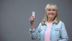 Εύθυμη ανώτερη κυρία που παρουσιάζει χάπια, αποτελεσματικό φάρμακο καρδιών, ενάντά στον ιό φάρμακα φιλμ μικρού μήκους