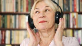 Εύθυμη ανώτερη μουσική ακούσματος γυναικών με τα ασύρματα ακουστικά Meloman χορός συνταξιούχων στη μουσική απόθεμα βίντεο
