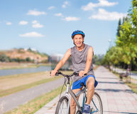 Εύθυμη ανώτερη τοποθέτηση με το ποδήλατό του σε ένα πεζοδρόμιο Στοκ εικόνα με δικαίωμα ελεύθερης χρήσης