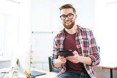Εύθυμη αρσενική ταμπλέτα συνεδρίασης και εκμετάλλευσης στο γραφείο Στοκ φωτογραφία με δικαίωμα ελεύθερης χρήσης