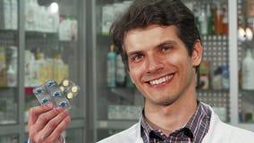 Εύθυμη αρσενική χαμογελώντας εκμετάλλευση δύο φαρμακοποιών φουσκάλες των χαπιών στοκ εικόνες
