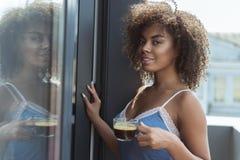 Εύθυμη αφρικανική δοκιμάζοντας κούπα γυναικών του ποτού Στοκ Φωτογραφίες