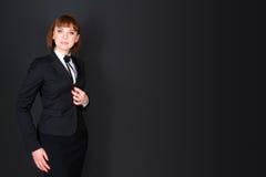 Εύθυμη βέβαια επιχειρησιακή γυναίκα που στέκεται στο σκοτεινό δωμάτιο γραφείων και που εξετάζει τη κάμερα Γοητευτική επιχειρηματί Στοκ εικόνα με δικαίωμα ελεύθερης χρήσης