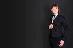 Εύθυμη βέβαια επιχειρησιακή γυναίκα που στέκεται στο σκοτεινό δωμάτιο γραφείων και που εξετάζει τη κάμερα Γοητευτική επιχειρηματί Στοκ Εικόνα