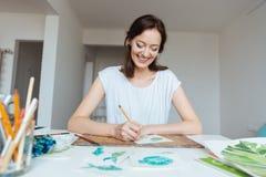 Εύθυμη γυναίκα ζωγράφος που κάνει τα σκίτσα στο εργαστήριο Στοκ εικόνα με δικαίωμα ελεύθερης χρήσης