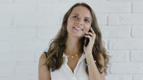 Εύθυμη γυναίκα με την κυματιστή τρίχα που μιλά στο smartphone απόθεμα βίντεο