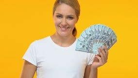 Εύθυμη γυναίκα με τη δέσμη των δολαρίων που παρουσιάζουν αντίχειρες, εύκολα χρήματα, λαχειοφόρος αγορά απόθεμα βίντεο