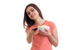 Εύθυμη γυναίκα με τη TV μακρινή και pop-corn τους κινηματογράφους προσοχής Στοκ φωτογραφία με δικαίωμα ελεύθερης χρήσης