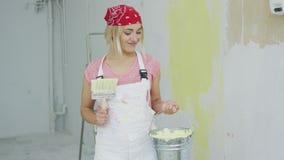 Εύθυμη γυναίκα με τον κάδο βουρτσών και χρωμάτων απόθεμα βίντεο