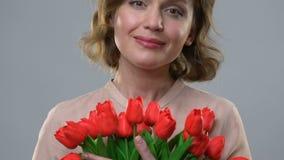 Εύθυμη γυναίκα που απολαμβάνει τη μυρωδιά των λουλουδιών, έννοια της θηλυκότητας και της ομορφιάς απόθεμα βίντεο