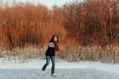 Εύθυμη γυναίκα που απολαμβάνει τον πάγο που κάνει πατινάζ σε μια παγωμένη λίμνη Στοκ Φωτογραφίες