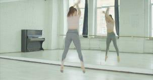 Εύθυμη γυναίκα που ασκεί τον εκφραστικό χορό στο στούντιο απόθεμα βίντεο