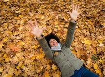 Εύθυμη γυναίκα που βρίσκεται στα ξηρά φύλλα φθινοπώρου Στοκ Εικόνα