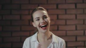 Εύθυμη γυναίκα που γελά και που θέτει στη κάμερα στο στούντιο με το τουβλότοιχο απόθεμα βίντεο